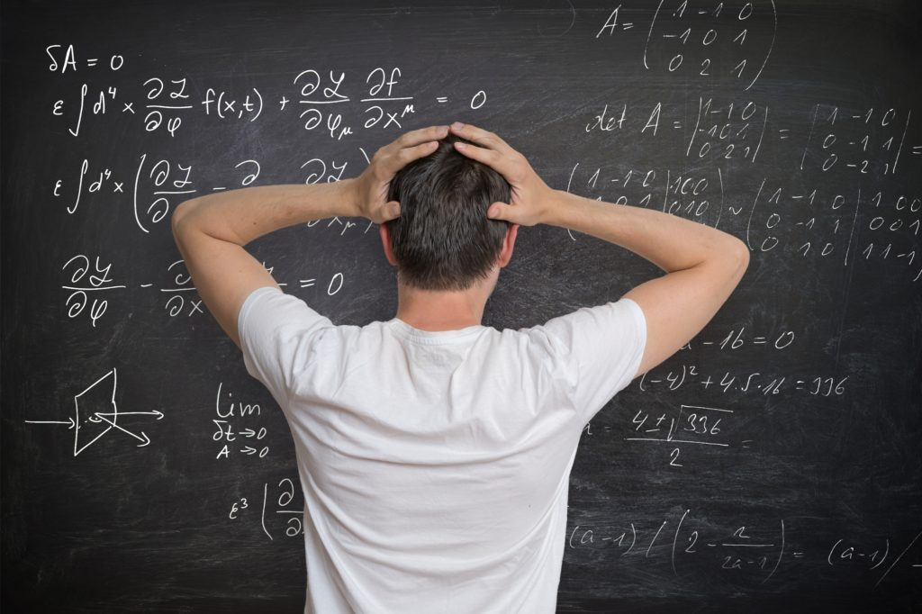 Young man is solving mathematical problem on blackboard